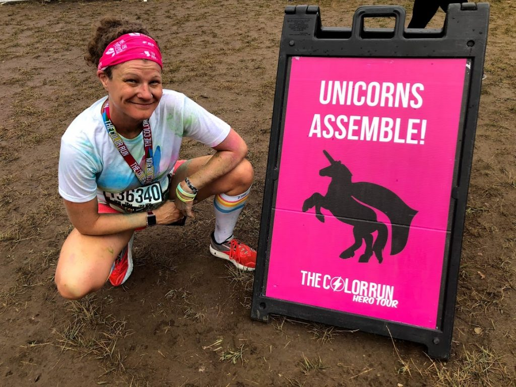 """Molly at the Color Run in a white t-shirt with colorful powder on it and a pink headband kneeling next to a pink sign that says """"unicorns assemble!"""""""